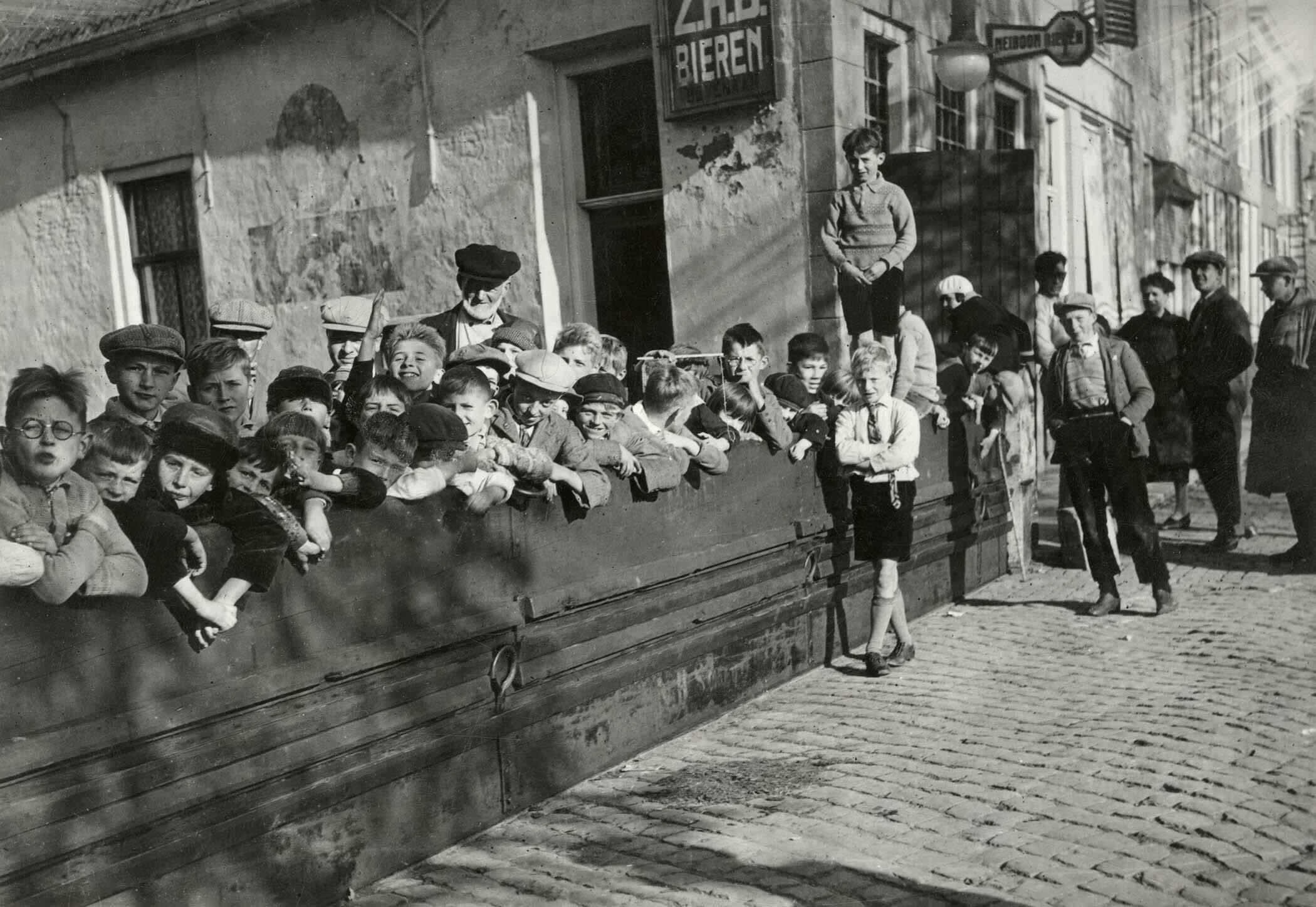 Foto van vloedplanken die aangebracht zijn voor een straat in Zierikzee op 6 november 1931. De plaatselijke jeugd poseert achter de plank en het café is gered.