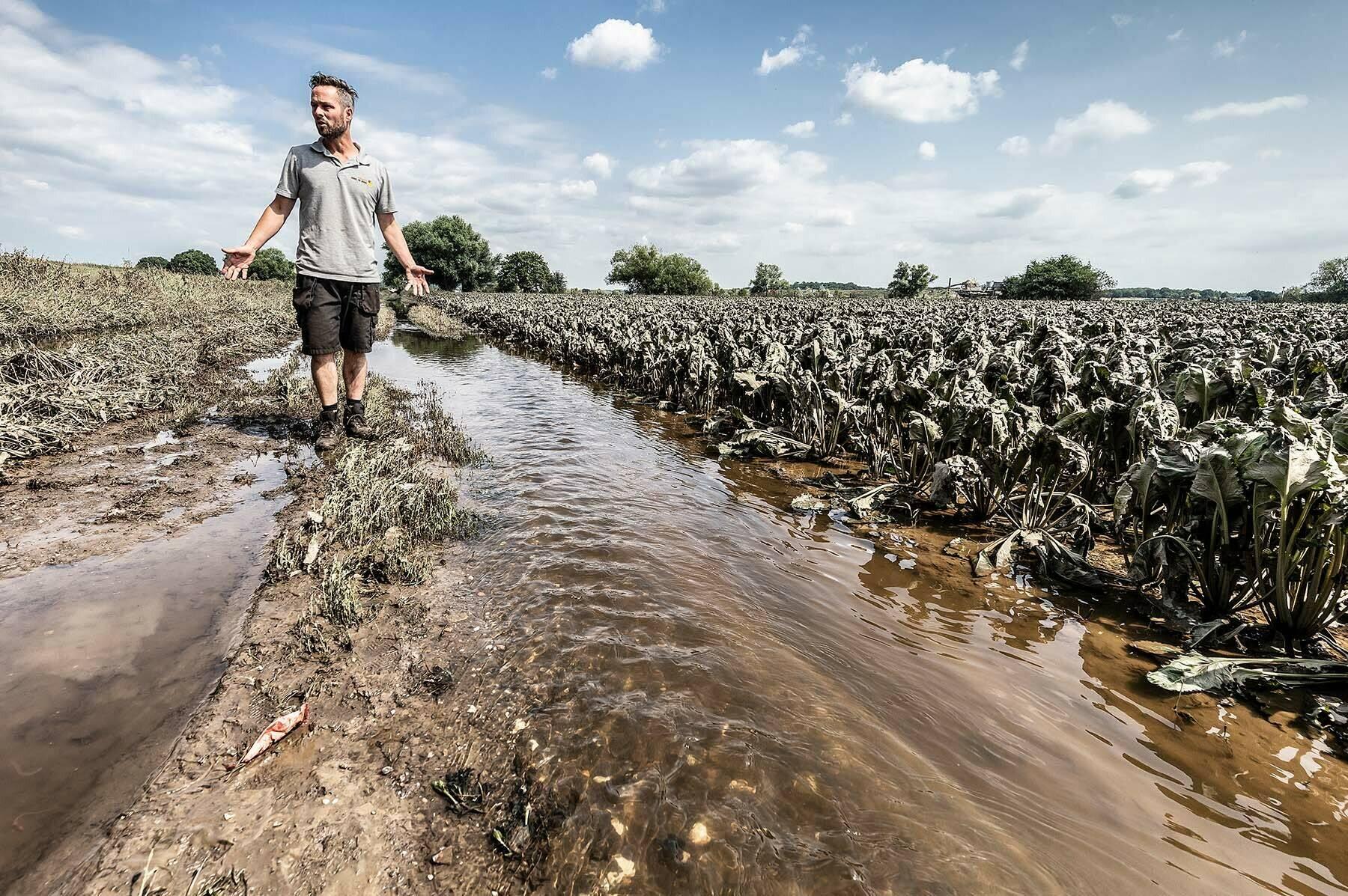 Foto van akkerbouwer op ondergelopen land als gevolg van de overstromingen in  2021.