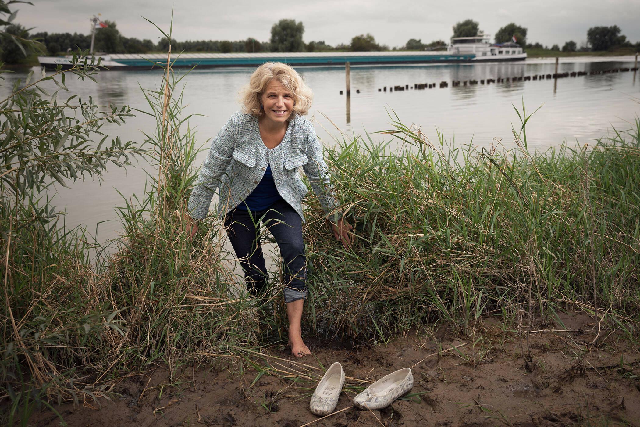 Foto van Michelle Talsma die uit een rivier water stapt. Haar schoenen staan in de modder op de kant.