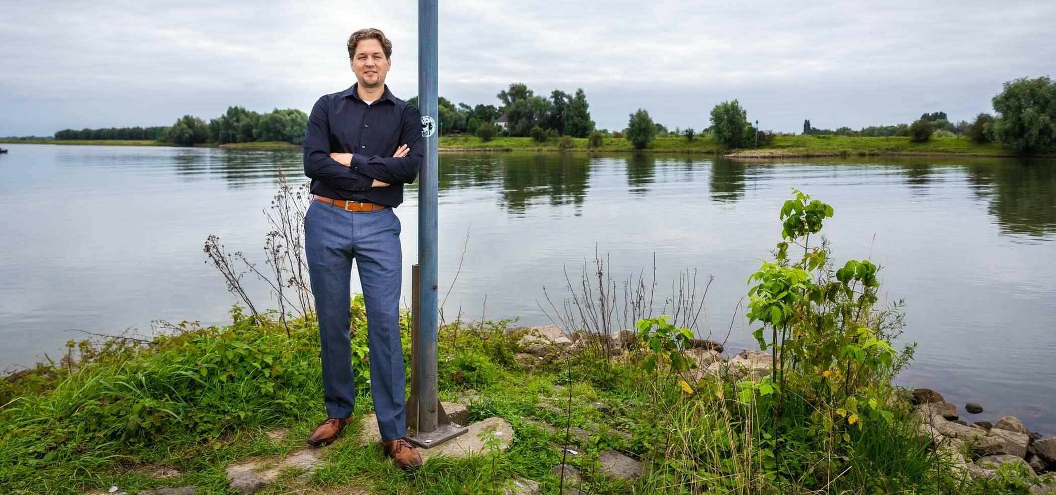 Foto van Martijn van Staveren leunend tegen een paal voor een meertje.